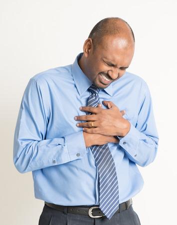 dolor de pecho: Empresario indio angustia, presionando sobre el pecho con expresi�n de dolor, en el fondo plano Foto de archivo