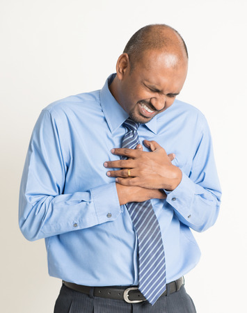heartache: Indian businessman heartache, pressing on chest with painful expression, on plain background