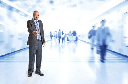 african american handshake: Full body Indian businessman offering hand shake at corridor, inside business building with motion blurred people as background. Stock Photo