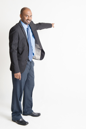 Full body Indian businessman pointing away to copy space, on plain background. photo