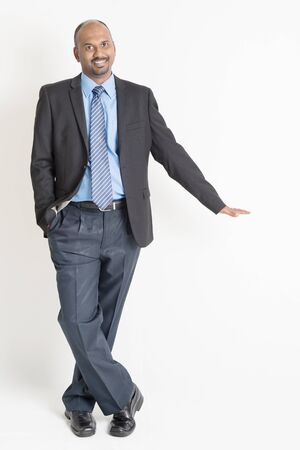 asian businessman: Full body Asian Indian businessman putting hand on invisible banner over plain background