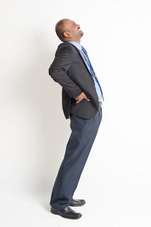 ejecutivos: Todo el cuerpo empresario indio dolor de espalda, la celebraci�n de su columna vertebral con expresi�n de la cara dolorosa, de pie en el fondo plano.