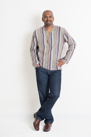 mature male: Full length confident Indian guy in casual wear standing on plain background with shadow.