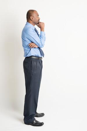completo: Vista de perfil de cuerpo completo hombre de negocios indio mano en la barbilla mirando al espacio de la copia en blanco, de pie en el fondo plano con la sombra Foto de archivo