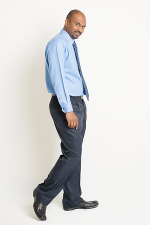 turn back: Side view Indian businessman walking and turn back head looking at camera, on plain background. Stock Photo