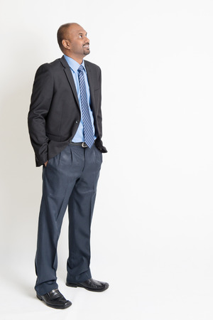 Indian businessman smiling and looking away towards copy space, full body standing on plain background. Stok Fotoğraf - 37407162