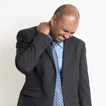 dolor muscular: Dolor de hombro empresario indio, la celebración de su cuello con la expresión de la cara dolorosa, de pie en el fondo plano.