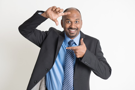 senior business: Cheerful Indian businessman making fingers frame and peeping through, on plain background