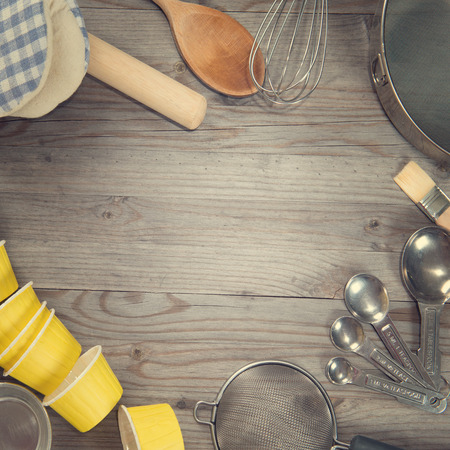 kitchen tools: Various baking tools arrange from overhead view on wooden table in vintage tone. Copy space on middle with square composition. Stock Photo
