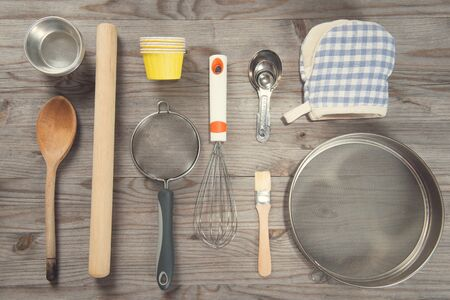baking ingredients: Various baking tools arrange from overhead view on wooden table in vintage tone. Stock Photo