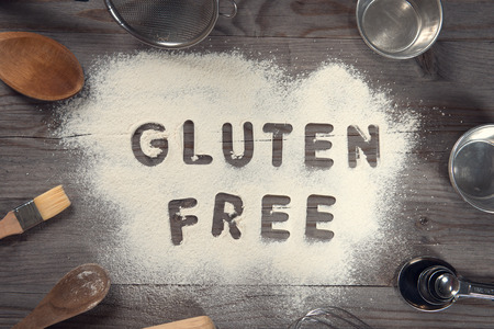 Word gluten free written in white flour on a old wooden table from top view in vintage tone, surrounding by baking tools.