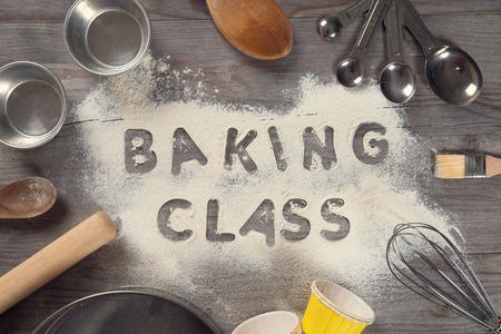 Slovo pečení třída psaný v bílé mouky na starý dřevěný stůl z pohledu shora ve vrcholném tónu, okolní pečením nástroji.