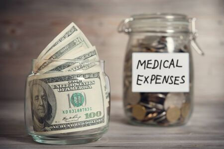 Dollars and coins in glass jar with medical expenses label, financial concept. Vintage tone wooden background with dramatic light.