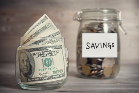 ドルとガラスのコインは、ラベル、金融の概念を保存すると jar します。ビンテージ トーン劇的な光と木製の背景。