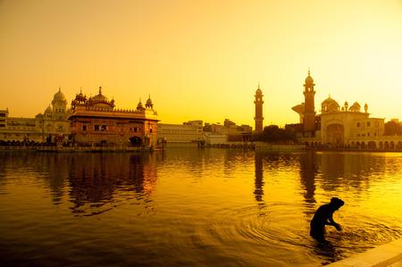 orando: Puesta de sol en el Templo Dorado de Amritsar, Punjab, India.