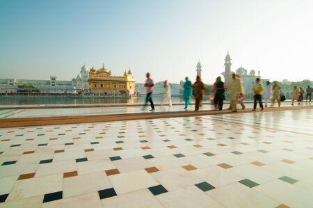 amritsar: Group of Sikh pilgrims walking by the holy pool, Golden Temple, Amritsar, Pun jab state, India, Asia