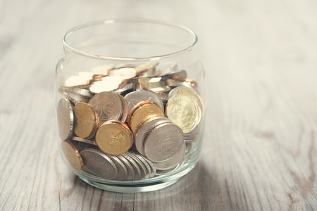 old coins: Coins in glass money jar, on wooden background.