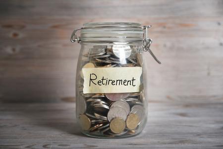 退職金ラベル、金融の概念とガラスの瓶にコイン。劇的な光とヴィンテージの木製の背景。