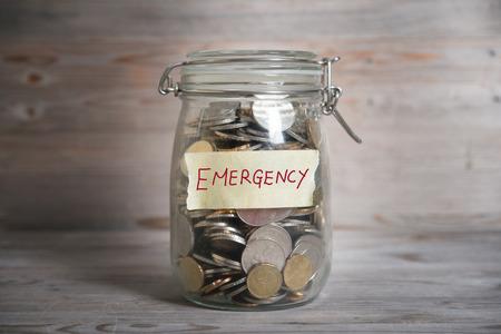 fondos negocios: Monedas en el dinero tarro de cristal con etiqueta de emergencia, concepto financiero. Fondo de madera de la vendimia con la luz dramática.