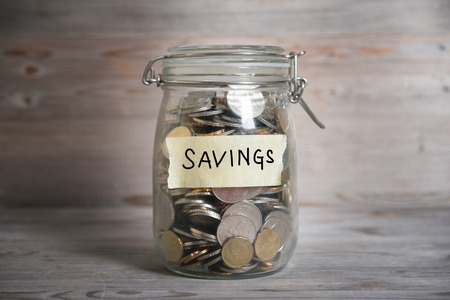 saving tips: Coins in glass money jar with savings label, financial concept. Vintage wooden background with dramatic light.
