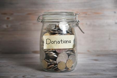 Munten in glazen pot geld met donaties label, financiële concept. Vintage houten achtergrond met dramatische licht. Stockfoto