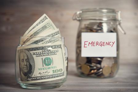 fondos negocios: Dólares y monedas en frasco de vidrio con etiqueta de emergencia, concepto financiero. Fondo de madera tono de la vendimia con la luz dramática.