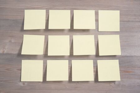 Sticky notes on wooden background, in vintage tone. photo
