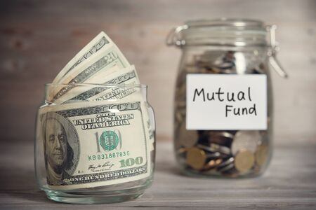 mutual fund: Dollars and coins in glass jar with mutual fund label, financial concept. Vintage tone wooden background with dramatic light.