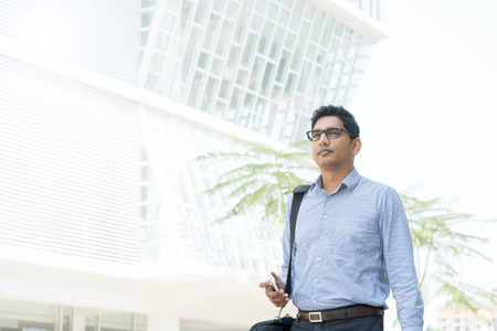 indian professional: Young business man walking by a modern office building.