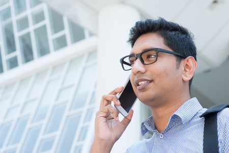 indian boy: Young Indian business man talking on phone in front modern office building.