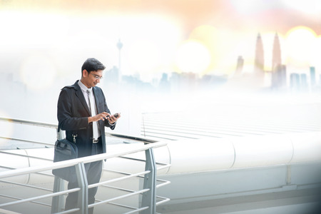 Asian businessman using smartphone, standing at modern office building, skyline at background.