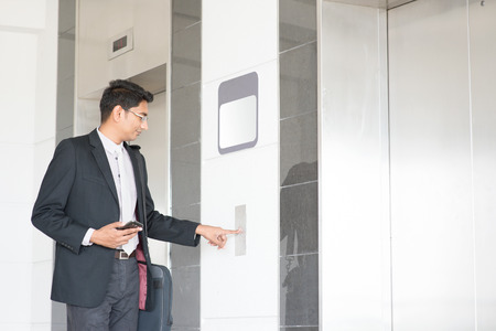 people in elevator: Young Indian businessman pressing on elevator button, waiting door open to enter inside the lift.