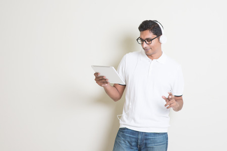Portrait of handsome Indian guy using tablet pc and enjoying music, standing on plain background with shadow, copy space at side. photo