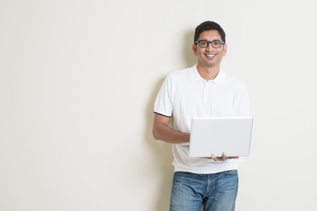 african business man: Portrait of handsome Indian guy using laptop computer, standing on plain background with shadow, copy space at side.