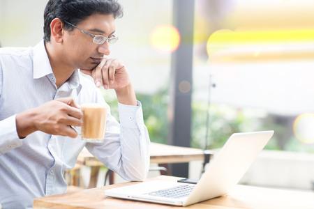 Человек с помощью портативного компьютера во время питья чашку горячего молока чай, открытое кафе.