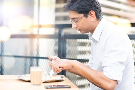 Asian Indian businessman eating roti at cafeteria. photo