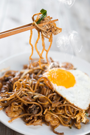 asian noodle: Stir fried char kway teow with prawns and chopstick over wooden background. Stock Photo