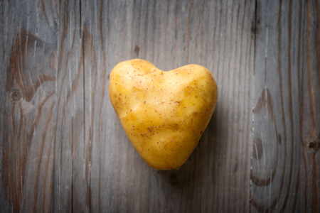 spud: Heart shaped golden potato spud on Wooden Table Background, Concept and Idea of Food Cook Rustic Still life Style. Dramatic light table setting. Stock Photo