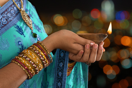 Diwali or festive of lights. Traditional Indian festival, woman in sari hands holding oil lamp, copy space at side.