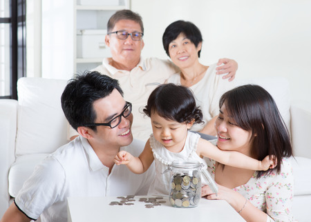 asian toddler: Toddler counting coins. Asian family money savings concept. Multi generations living lifestyle at home. Stock Photo