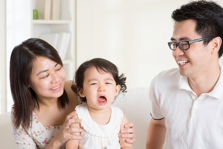 Parents is comforting their crying daughter. Asian family at home. photo