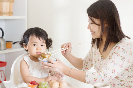 mom's house: Asian mother feeding her child at home.