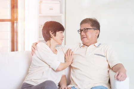 Senior couple chatting, sitting on sofa at home. Living lifestyle of Asian family. Stock Photo
