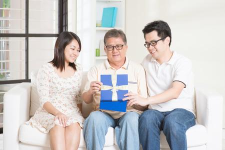Gelukkige vader dag. Vader die een verbaasde geschenk van zijn jonge kinderen. Familie wonen lifestyle thuis.