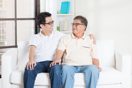 grown: Asian senior father and adult son having conversation at home. Family living lifestyle.