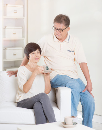 Senior couple having tea and relaxing, sitting on sofa at home. Living lifestyle of Asian family. photo