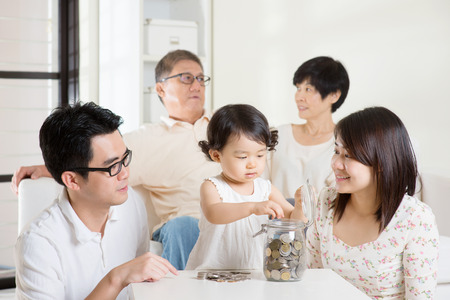asian toddler: Toddler putting coins into money jar. Asian family money savings concept. Multi generations living lifestyle at home. Stock Photo