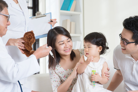 baby crying: Child vaccination. Family doctor vaccines or injection to baby girl. Pediatrician and patient. Stock Photo