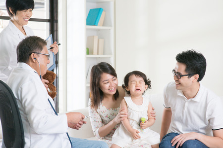 asian baby: Child vaccination. Family doctor giving injection or vaccines to baby girl. Pediatrician and patient.