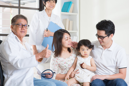 Pediatrician giving a thumb up after examined child. Pediatrician and patient healthcare concept. Stock Photo